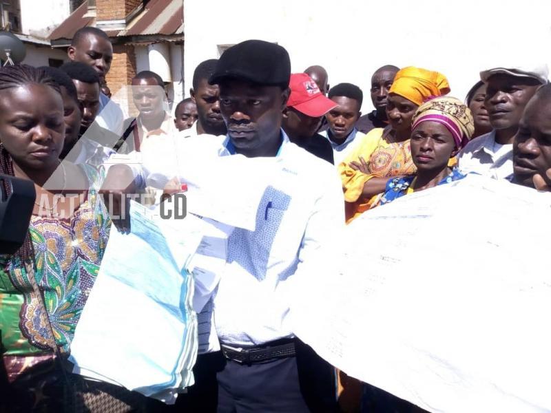 Le CACH Bukavui brandit les bulletins de vote qu'elle affirme avoir ramassé dans une rivère au village Cidodobo.