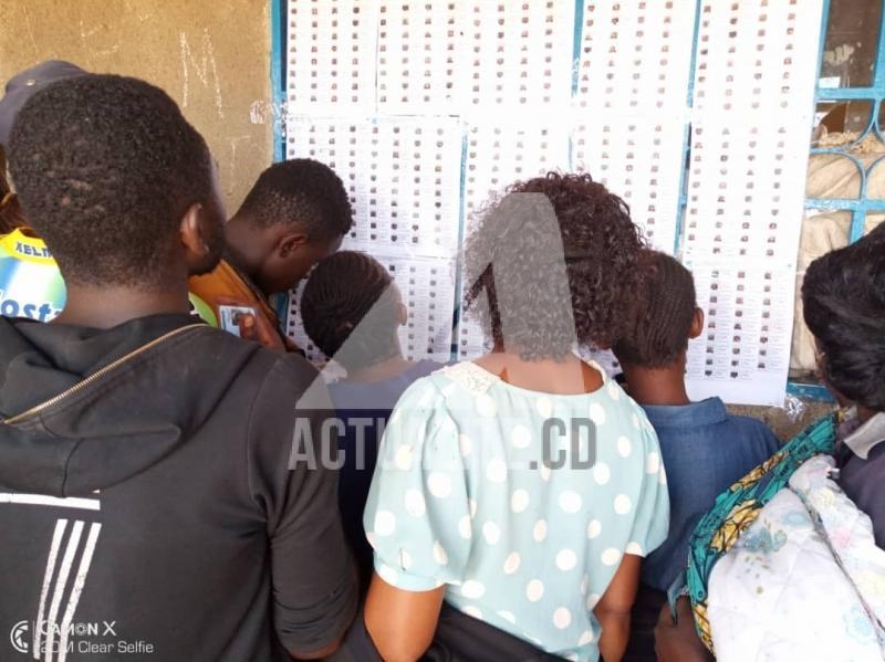 Les électeurs en train de consulter les listes électorales devant un bureau de vote.